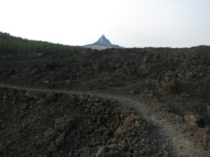 Trail through lava rocks, with one of the Sisters in the background.